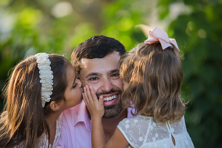 daddy getting kisses from daughters showing family love at Bastrop Hyatt Lost Pines How to Find Perfect Austin Family Photo Locations