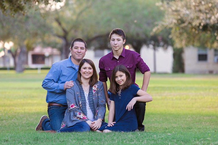 Family of 4 sitting pose on the grass What to Wear During your Portrait Photography Session