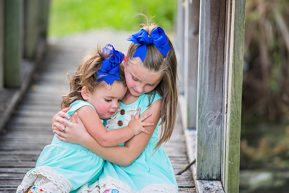 Importance of Austin Family Photographers sisters hugging at Quarries Park in Northwest Austin