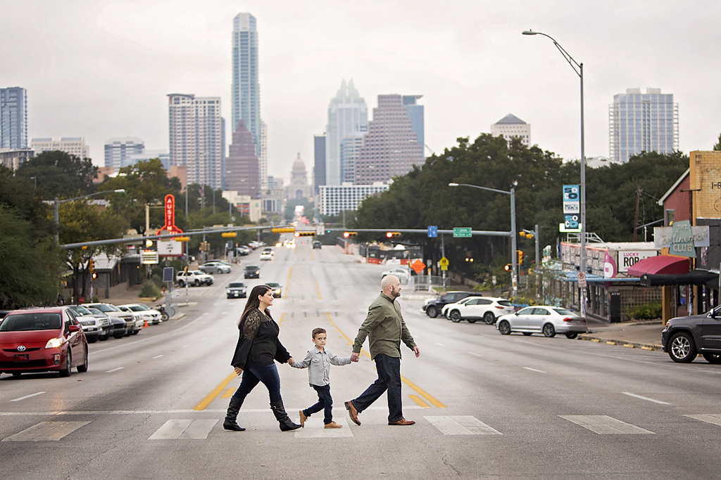 Best Time to Book Outdoor Portrait Photography South Congress Avenue family walking across street with Texas State Capitol in the background