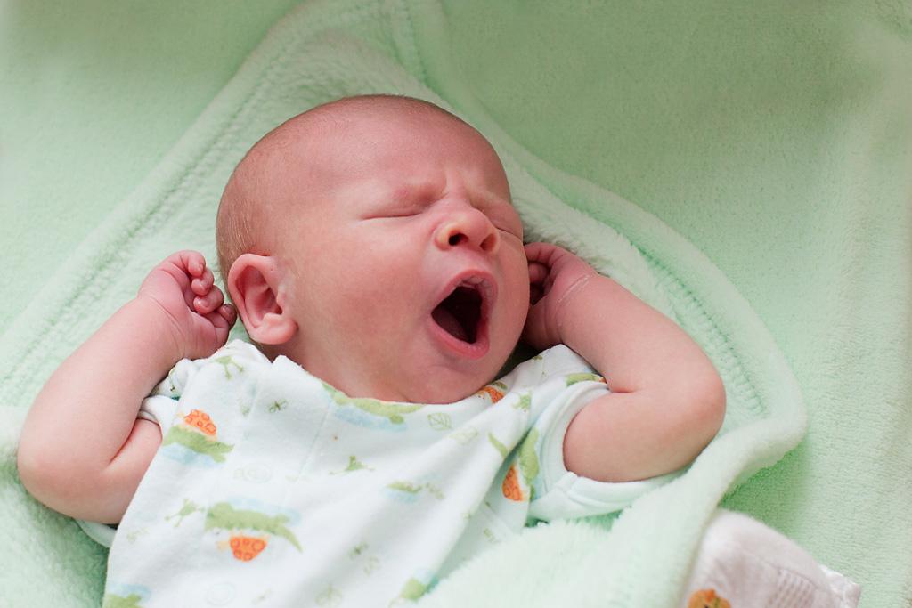 Austin Lifestyle Newborn Photography Session Tips - newborn yawning in crib -Austin, Texas - Jama Pantel Photography - www.jamapantel.com