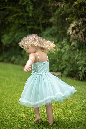 Austin Photographers girl in green dress twirling outside