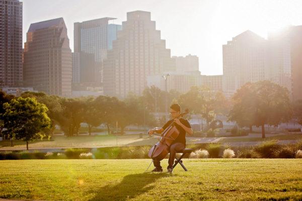 Austin Senior Photographer boy playing cello at sunrise with Austin skyline behind him