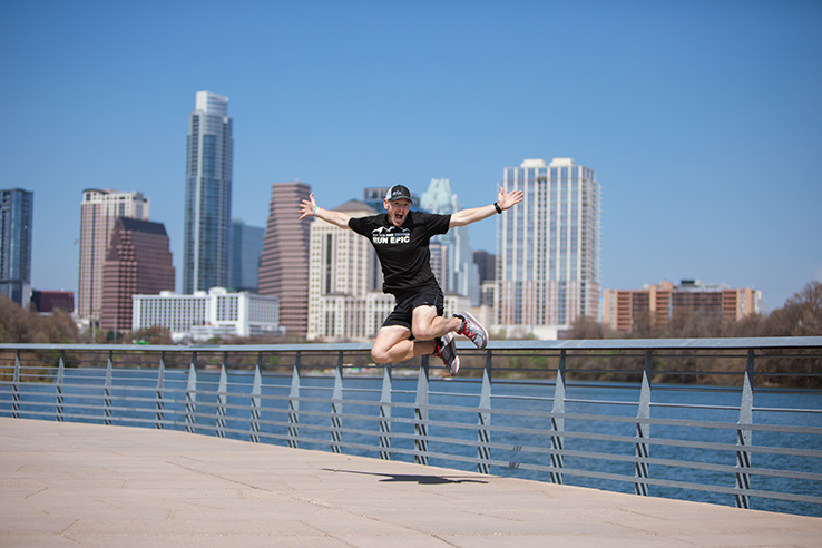 Austin personal branding photographer ultra runner jumping on lady bird lake hike and bike trail bridge with Austin skyline in background