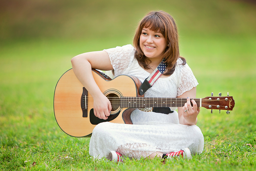 Girl playing guitar for senior portraits Austin at the State Capitol